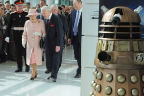 Queen Elizabeth II walks near to a Dalek from the Doctor Who television series as she visits the MediaCity in Salford, Manchester